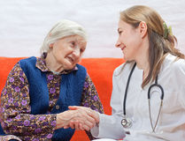 Old woman and the young doctor. Old woman and the sweet young doctor Stock Photography