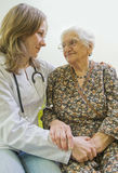 Old woman and young doctor. Old woman tells a story to the young doctor Stock Photo