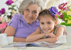 Old woman with a young girl drinking tea Stock Photos