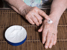Old womans  hands applying cream Royalty Free Stock Image