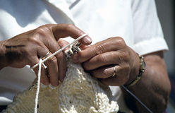 Old woman's hands producing knit ware. Royalty Free Stock Photography