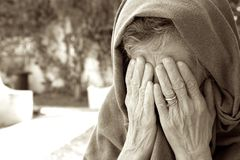 An old women closed her eyes with both hands. An old woman between 70 and 80 years old is hiding her tears from the interlocutor to whom she told her sad story Stock Images