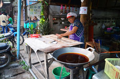 Old women cooking deep-fried doughstick. Or chinese donut or chinese bread for sale in Phare Thailand Phrae is one of the northern provinces (changwat) of royalty free stock image