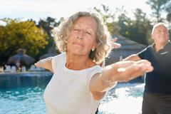 Old woman doing yoga exercise in workshop by the pool stock images