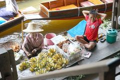 Old women and fatigue  boy  fried banana for sell in the boat at. Former times floating market on Dumnuen-saduak Thailand Stock Images