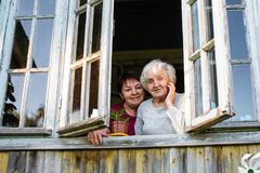 Old woman and her adult daughter from the window. stock photography