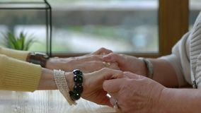 Old women holding hands. Ladies at the table. Support and understanding stock video footage