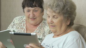 Old women holding the silver digital tablets. Old women sitting on a beige sofa at home. Each old woman holds the silver digital tablet stock footage