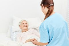 Old woman in bed in hospice or nursing home. Old women in hospice or nursing home is being comforted by a nurse Stock Photo