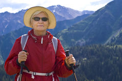Old women in mountain. Old women with mountains flowers Stock Photography