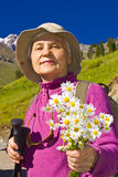Old women in mountain. Old women with mountains flowers Royalty Free Stock Images