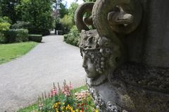 Old women`s figure on a giant vase. Snake flowers monster mythologic rock sculpture garden parc france montauban ancien vieille femme face tete head géant royalty free stock photos