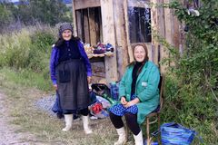 Old women smiling in Bukovina, Romania. Bukovina, Romania - 11 July 2014. Old friendly women selling mushrooms by the road Stock Image