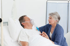 Old women taking care of her husband Royalty Free Stock Image