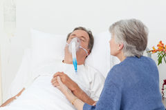 Old women taking care of her husband Stock Image