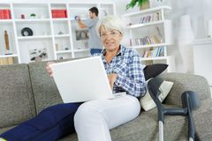 Old woman using laptop while sitting on sofa Royalty Free Stock Photos
