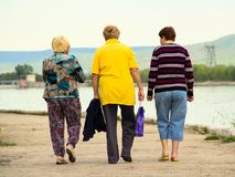 Old women walk along the embankment stock images