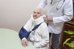 Old woman in a white bathrobe sits on a chair with a sling on her hand. The doctor puts on her neck an orthopedic collar. An old women in a white bathrobe sits stock photos