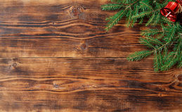 Old wood background with fir branch and red bell. Christmas background Royalty Free Stock Photo