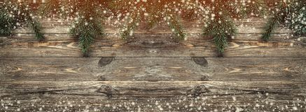 Old wood background with fir branches. Space for a greeting message. Christmas card. Top view. Effect of light and snowflakes.  stock photos