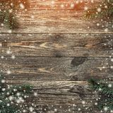 Old wood background with fir branches. Space for a greeting message. Christmas card. Top view. Effect of light and snowflakes.  royalty free stock images