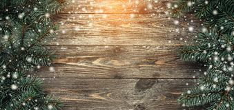 Old wood background with fir branches. Space for a greeting message. Christmas card. Top view. Effect of light and snowflakes.  royalty free stock photo