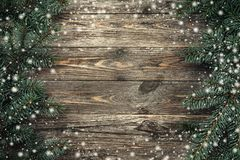 Old wood background with fir branches. Space for a greeting message. Christmas card. Top view. Effect snowflakes.  royalty free stock image