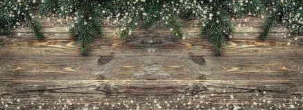 Old wood background with fir branches. Space for a greeting message. Christmas card. Top view. Effect snowflakes.  royalty free stock photos