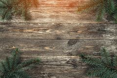 Old wood background with fir branches. Space for a greeting message. Christmas card. Top view. Light effect.  royalty free stock images