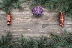 Old wood background with fir branches with toys. Space for a greeting message. Christmas card. Top view.  royalty free stock images