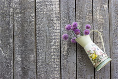 Old Wood background with flower pot on one side. Vintage old wood background with a pot of purple chives flowers hanging on one side Stock Photo