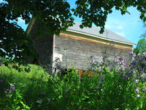Old wood barn outlined with green trees and purple flowers. Blue sky puffy clouds royalty free stock photos