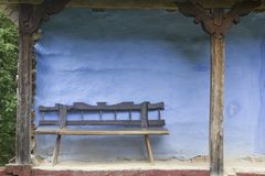 Old Wood Bench. With Blue Log House royalty free stock image