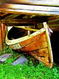 Old Wood Boat under a Dock. This is a old wood boat under a pier out by a lake in Norway on a Summer day Royalty Free Stock Images