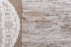 Old wood bordered by burlap and lacy cloth. Old wood bordered by lacy cloth and burlap background royalty free stock images