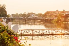 Old wood bridge with flagged and concrete bridge over the Wang River, Thailand. Old wood bridge with flagged and concrete bridge over the Wang River, glowing royalty free stock photos