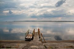 Old wood bridge pier with nobody against beautiful sky. Old wooden pier at a lake royalty free stock photography