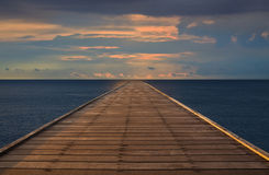 Old wood bridge to the sea with cloudy sky Stock Photos