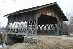 Covered Wood Bridge spans a stream Royalty Free Stock Images