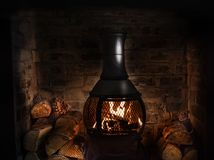 Old Wood Burner. Cast iron wood burner in old brick fireplace burning chopped wood, Concept image for Christmas, winter, Thanksgiving, stockings, festive royalty free stock images