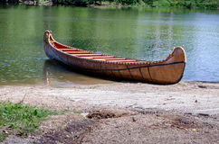 Wooden canoe on St Joseph River in Michigan. Old wood canoe  rests on the shore of the saint joseph River in Niles Michigan Royalty Free Stock Photography