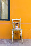 Old wood chair against orange wall Stock Photos