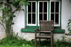 Old wood chair set in front of window of old country home Royalty Free Stock Image