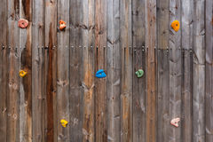 Old wood climbing wall with toe and hand hold studs. Grunge surface of old wood climbing wall with toe and hand hold studs royalty free stock photography