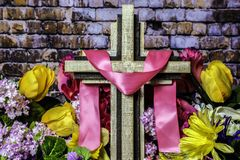 Old Wood Cross and Spring Flowers. Wood cross draped with pink ribbon surrounded by spring flowers with brick wall background Stock Photo