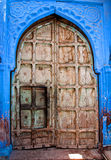 Old wood door with blue wall Royalty Free Stock Images