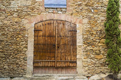 Old wood door closed on a cobble stone wall house Royalty Free Stock Photo
