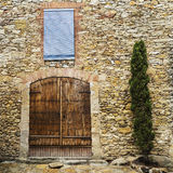Old wood door closed on a cobble stone wall house Stock Images
