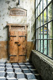 old wood door and a glass window  with cement wall Royalty Free Stock Images