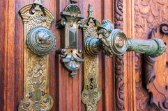 Old wood door handle on Peles museum, Sinaia Romania. Soldier fa. Ce graved in doorknob Stock Photography